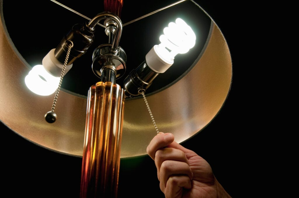 Man's hand pulling light switch chain for lamp with compact fluorescent bulbs