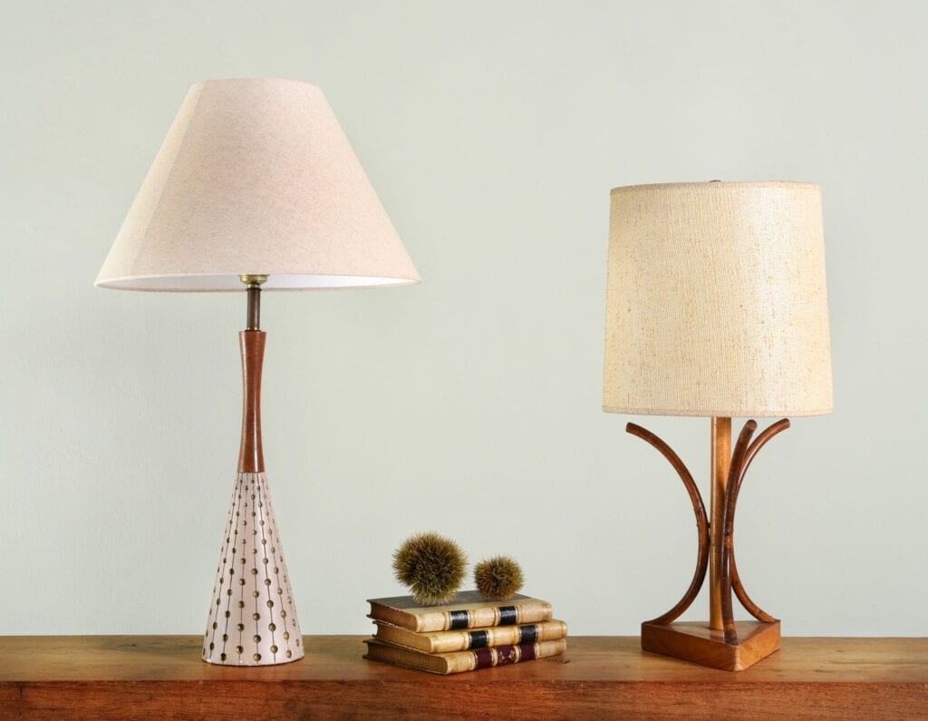 Books on wooden shelf between two vintage house lights with classic style lamp shades