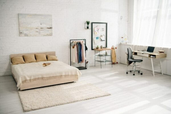 Cozy bedroom with big bed and workplace with laptop