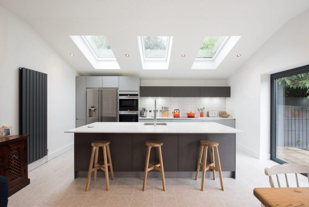 A general view of a modern fitted grey kitchen with large island, breakfast bar, white walls and sky light windows  within a home