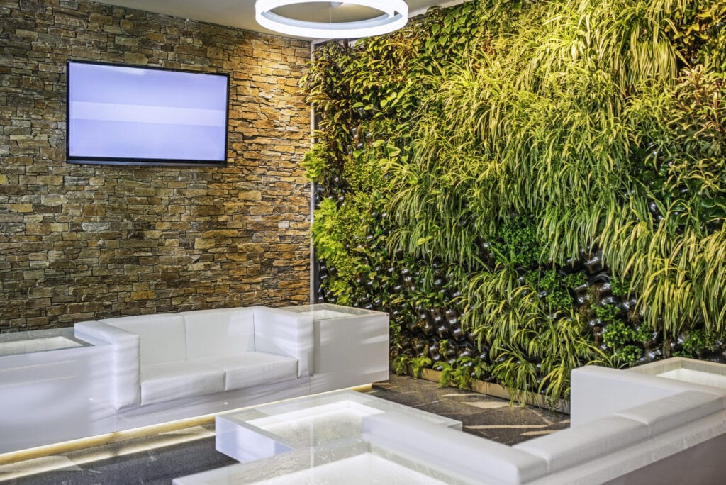 A modern designer lobby area with a flatscreen TV on a brick wall, white couches and a glass coffee table and plants growing out of a wall.