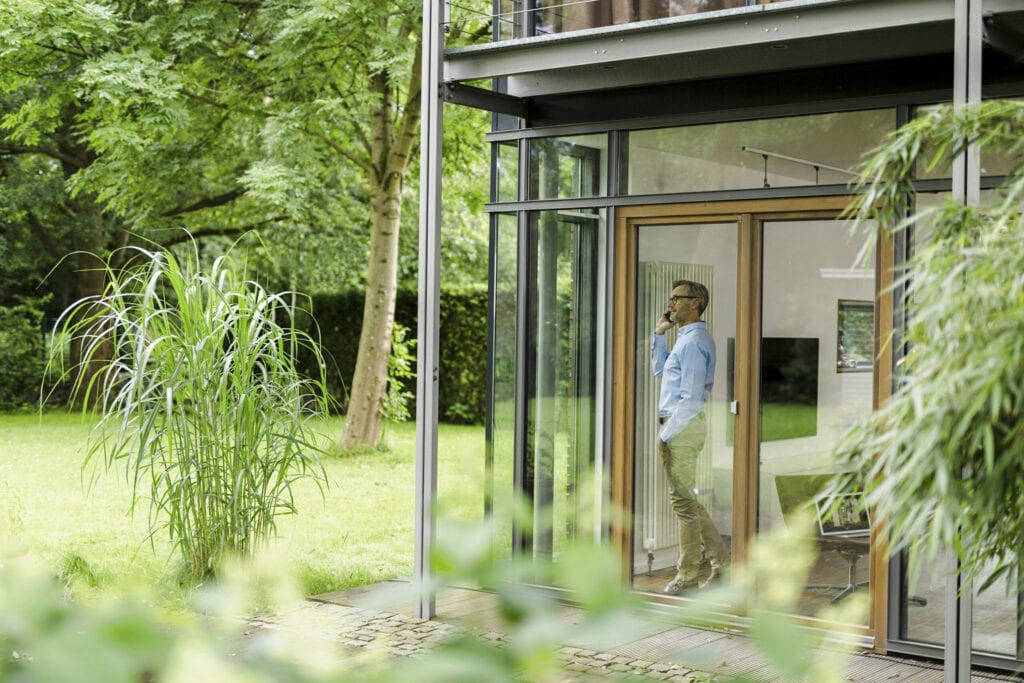 A grey haired man at home in his design house, germany