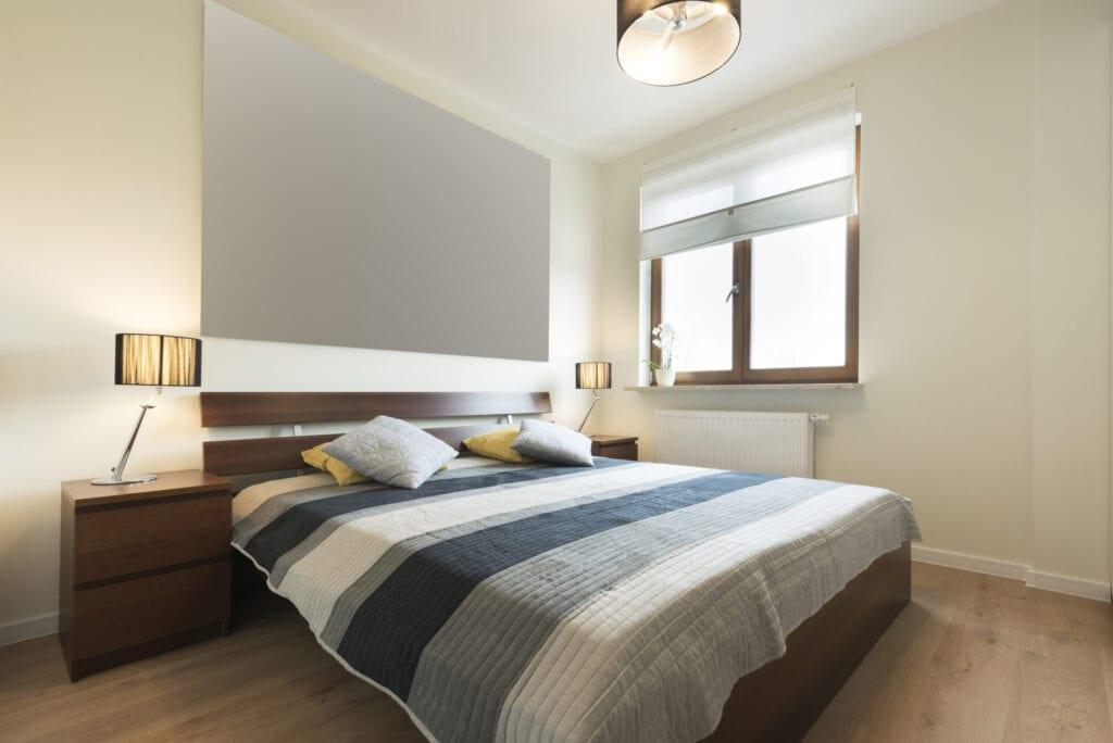 Modern bedroom in beige finishing and wooden floor
