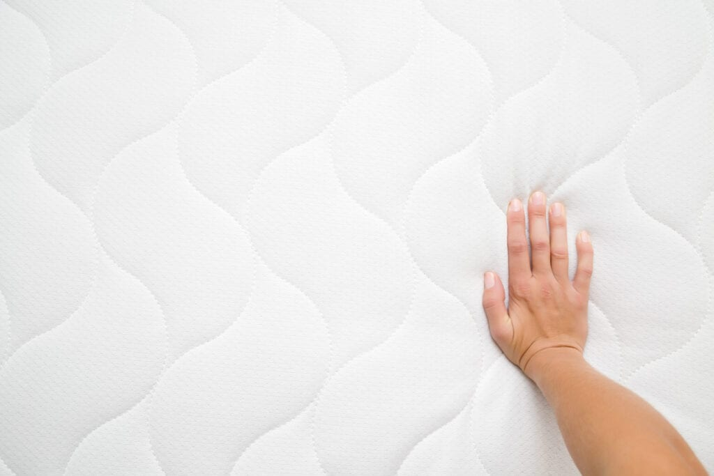 Woman's hand pressing on white mattress. Checking hardness and softness. Choice of the best type and quality. Point of view shot. Copy space. Empty place for text or logo. Top view. Close up.