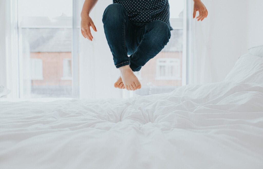 Cute little girl bouncing on a white bed in a bright room. Conceptual with space for copy.