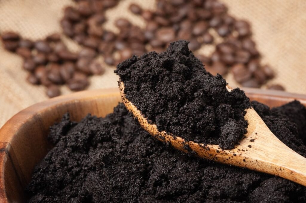 Coffee grounds in wooden bowl with spoon