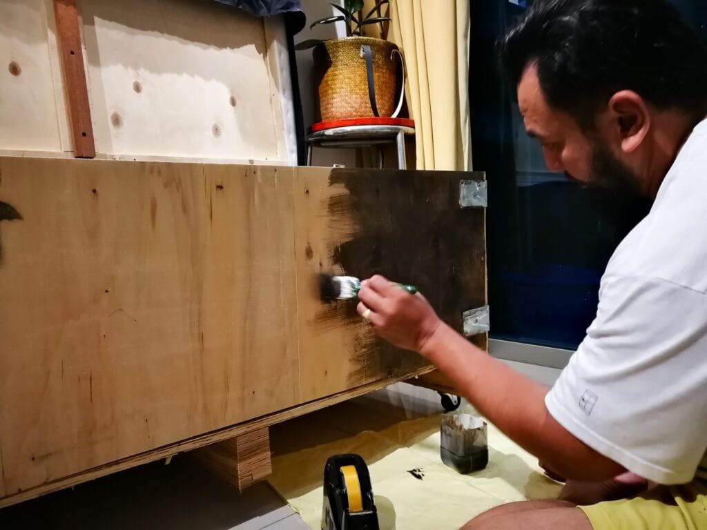 man painting furniture