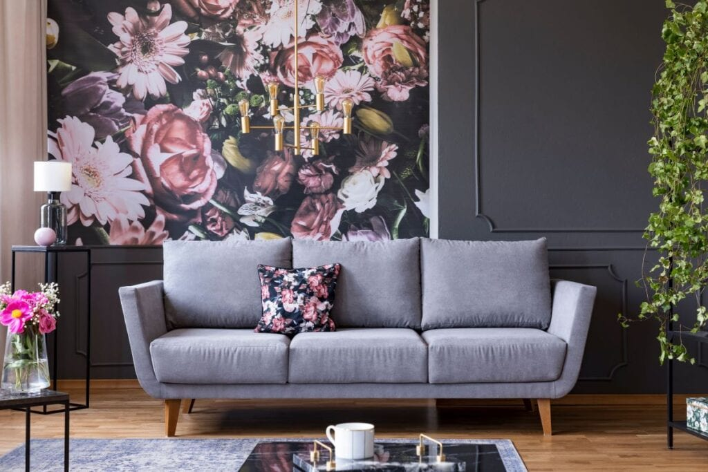 Gray couch with floral patterned pillow that matches floral wallpaper
