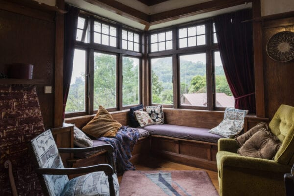 Living room in 1920s bungalow with vintage furniture and view to surrounding woodland