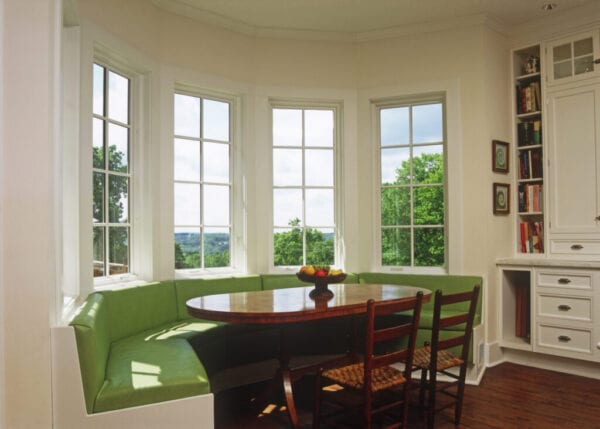 Sunny breakfast nook with green banquette seating