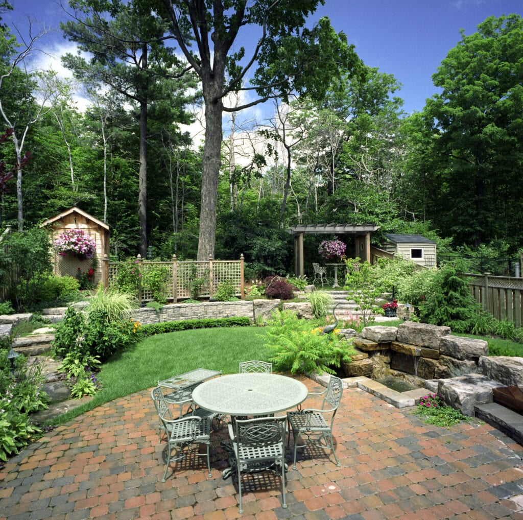 Backyard garden with patio terrace and water feature.