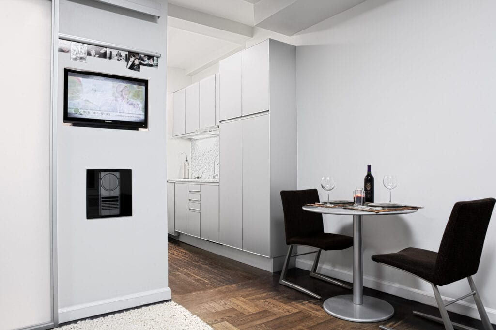 view of kitchen with designer cabinetry, sink, hidden dishwasher, inlayed television & stereo,  and dining area in studio apartment
