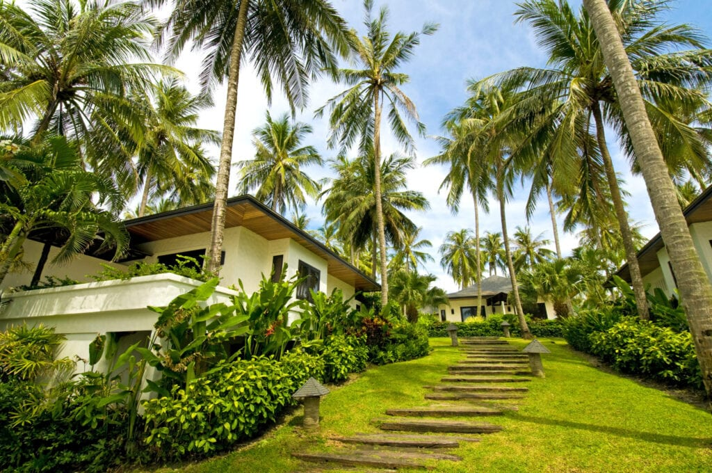 """""""Modern, luxury and exotic villa in the tropic island. Visible are many villas in the luxury resort, beach chairs and tables, fantastic cloudscape, many palm trees and green grass in the yard.See more images like this in:"""""""