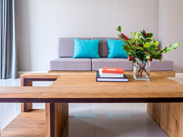 Flower vase on modern table top with gray sofa