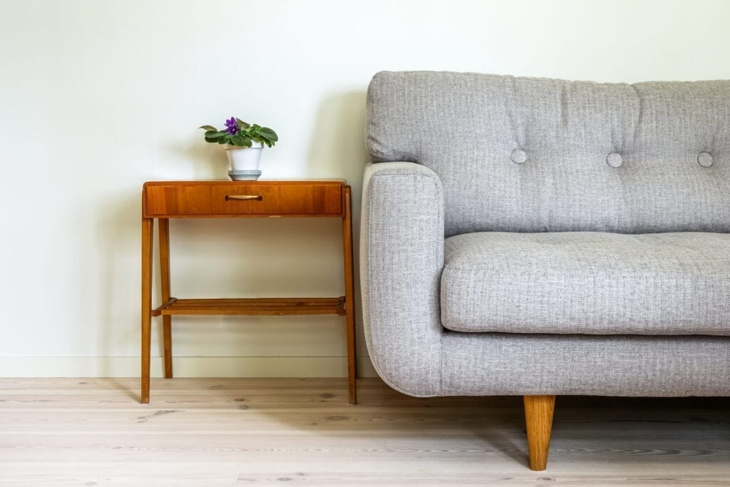 Modern retro interior. A gray couch and vintage table with a potted plant. Empty white wall in background.