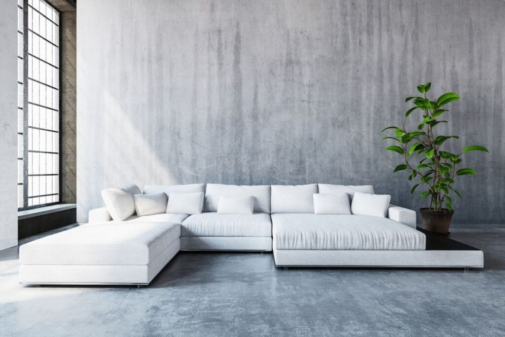 Modern white sofa in industrial living room with concrete walls and floors