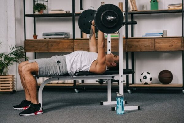 Man lifting weights in home gym with rubber flooring