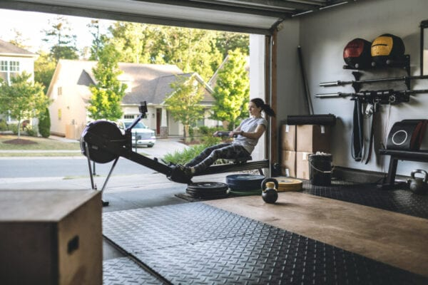 Active woman exercising on a rowing machine in her home garage gym during covid-19 pandemic.
