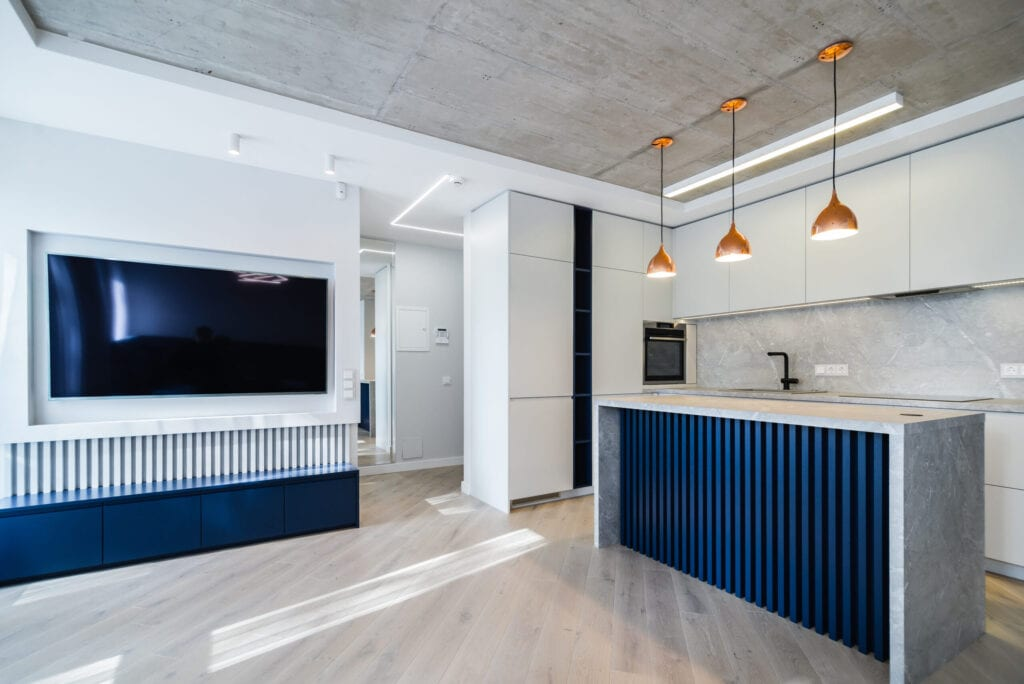 Modern and urban apartment interior with white colors, some plain concrete details and some blue colors. Living room connected with kitchen.
