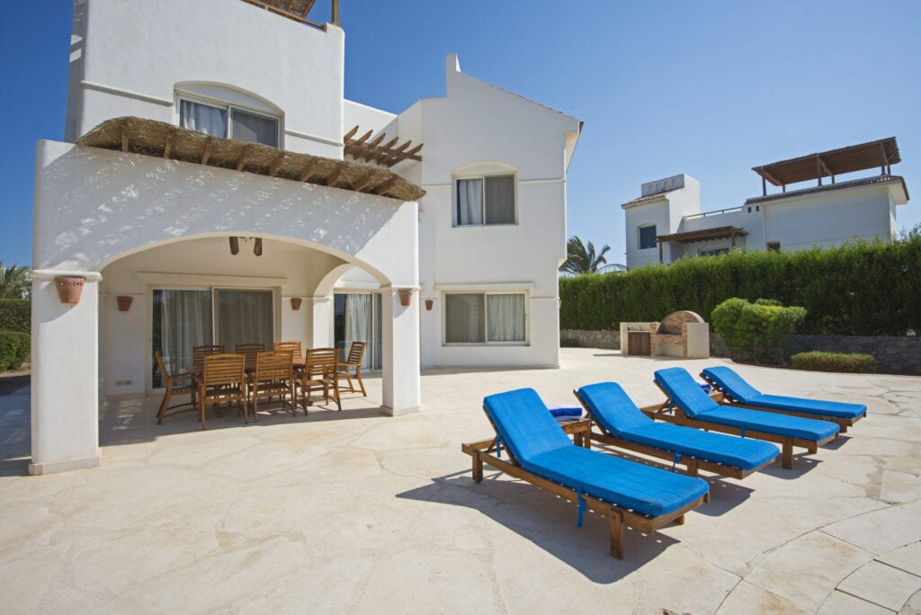 Luxury villa show home in tropical summer holiday resort with sun chairs on outdoor patio terrace area