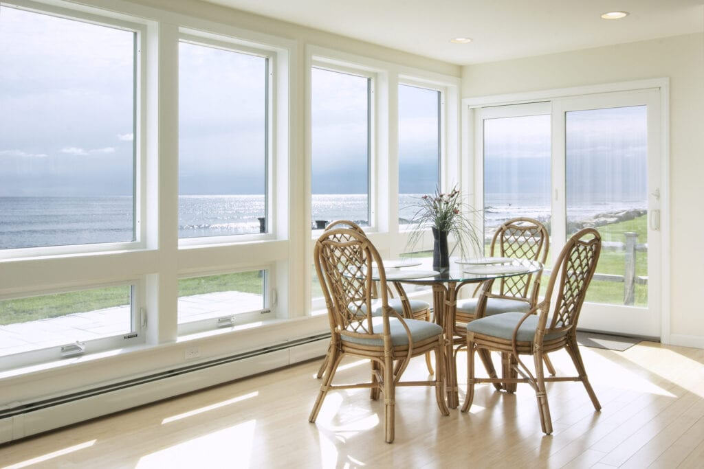 A small breakfast table sits in a sun room over looking the ocean.