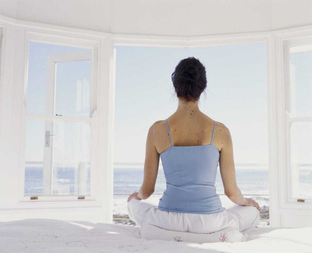 Young woman meditating on bed facing open window, rear view