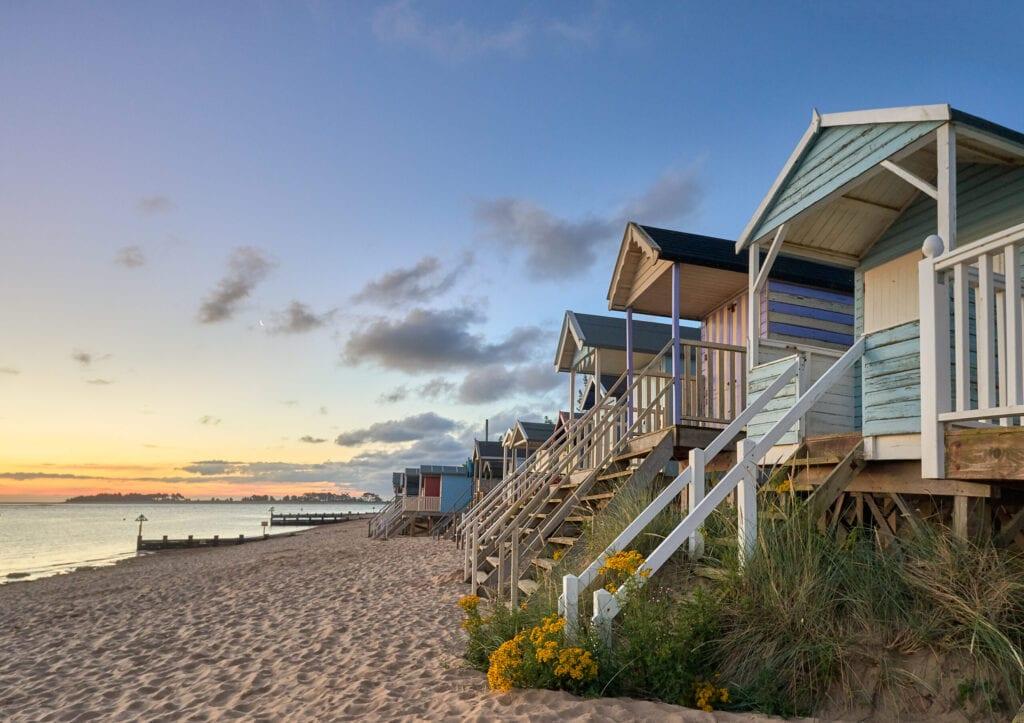 Early morning summer sunrise illuminates the row of beautifully coloured beach huts on the North Norfolk coast at Wells next the sea.