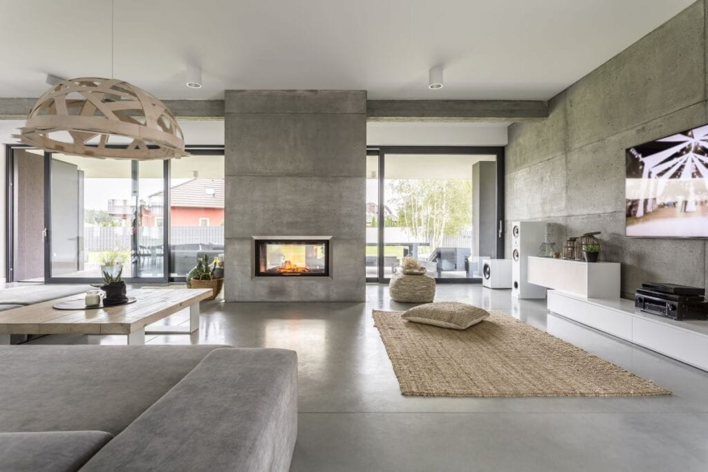 Interior of industrial home with floor to ceiling windows and fireplace