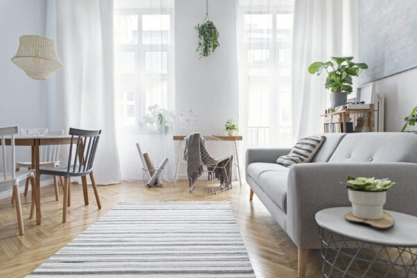 Modern scandinavian living room with design furniture, family table, plants, bamboo bookstand and wooden desk. Brown wooden parquet. Abstract painting on the white wall. Nice apartment.