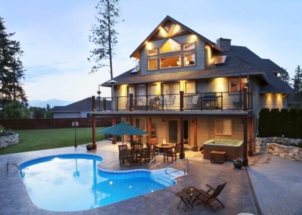 Canada, British Columbia, Kelowna, Exterior of large illuminated house by swimming pool at dusk