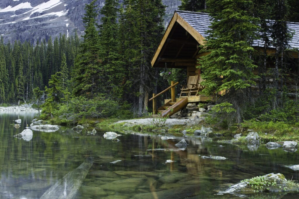 Evening shot of a log cabin at Lake O'Hara, BC, Canada. Rocks are seen beneath the water surface.  Beautiful scenic vacation get away.
