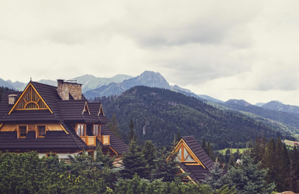 Poland - August 17, 2014: Mountain scene with wooden idyllic country estates with wood shingle roof in Zakopane, Poland.