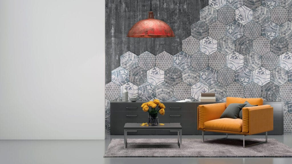 Living room interior with vibrant orange armchair, carpet, coffee table with flowers, hexagonal tiles on the wall, pendant light above, decorative ornate design. blank white wall for copy space artist template