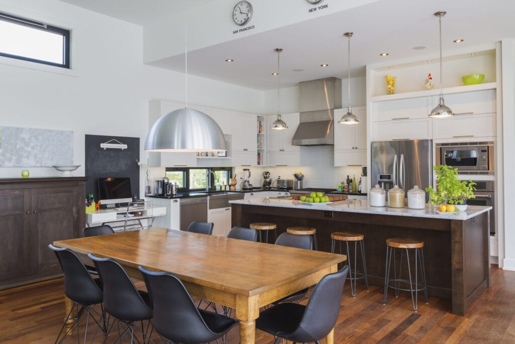 Open-concept dining and kitchen area with antique dining table with black leather and plastic chairs, marble top wooden island with painted black steel and exotic wood barstools, white cabinets inside a luxurious modern cube style house, Quebec, Canada. This image is property released. CUPR0343