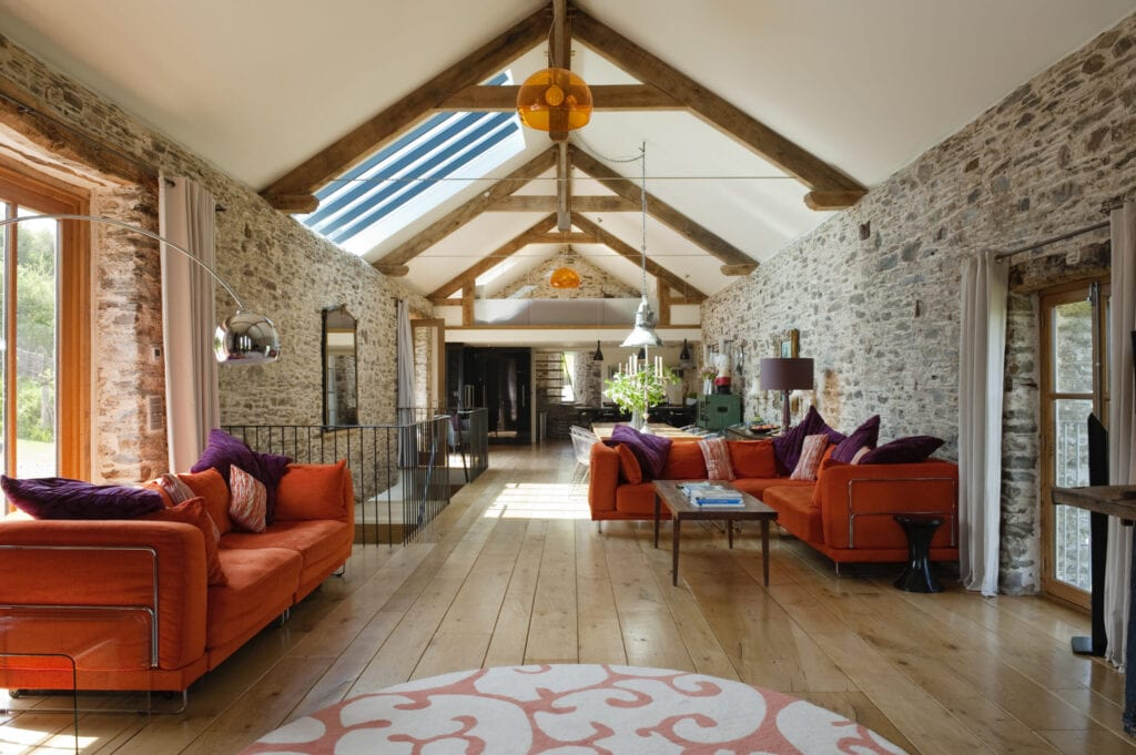 18th century Devon long barn conversion with L-shaped seating unit from Ikea on mezzanine floor