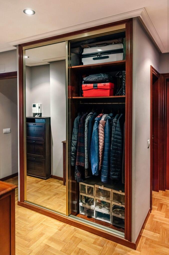Built-in wardrobe open with mirror doors in the corridor of an apartment
