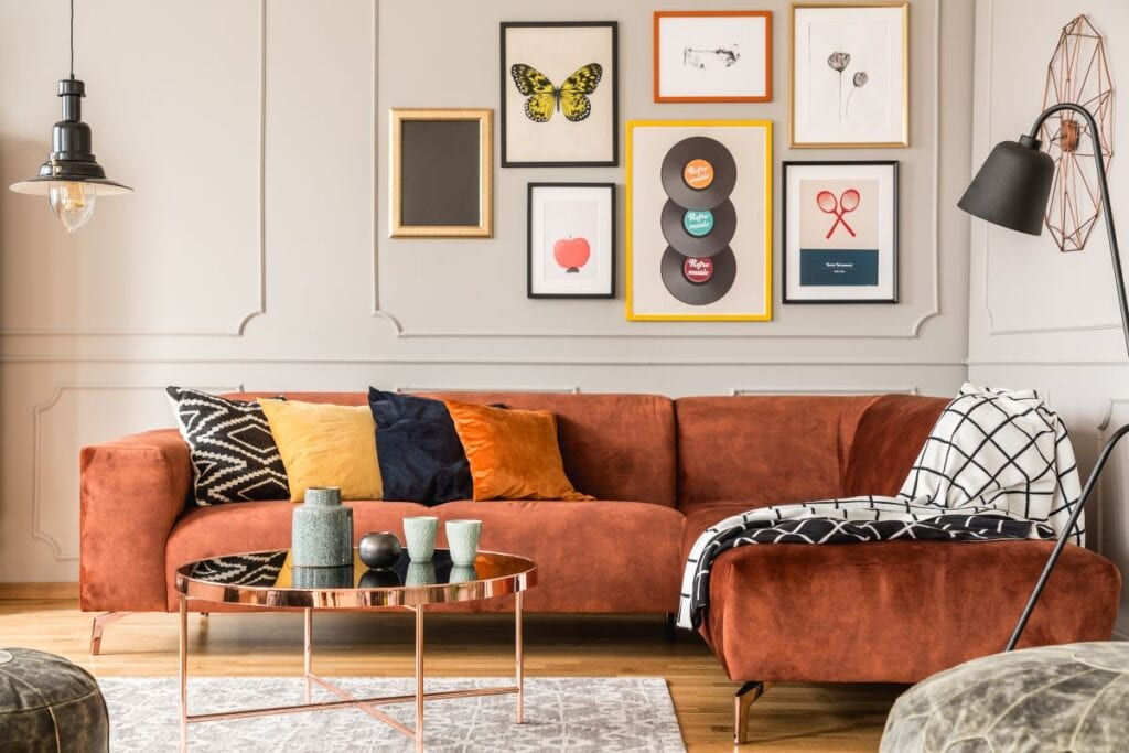 Eclectic living room with orange velvet sectional and mirror table