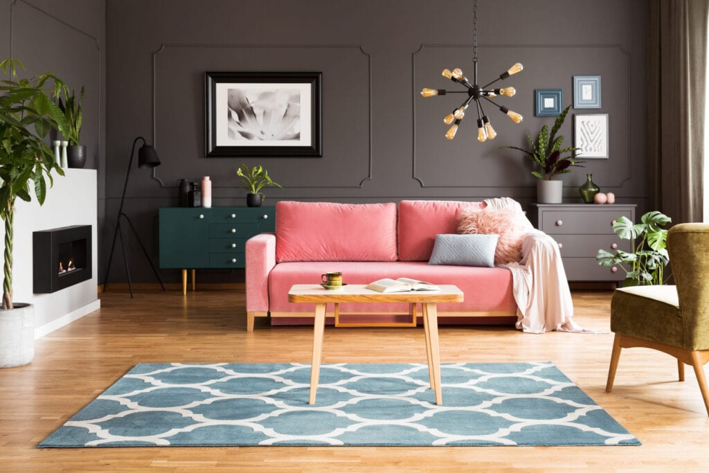 Grey interior of living room with pink sofa