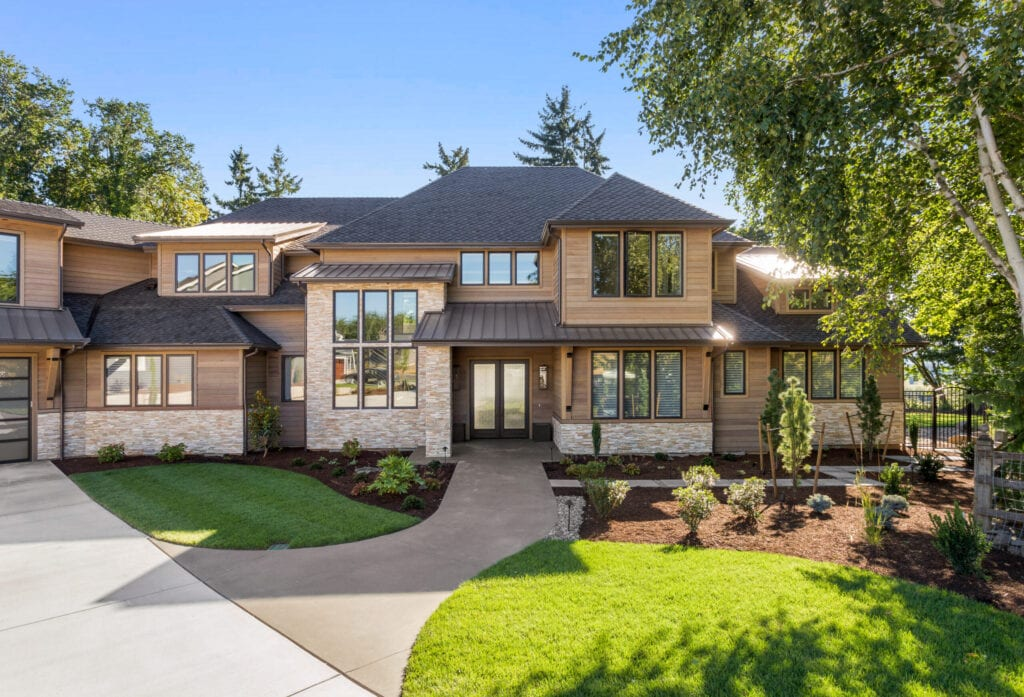 of home with manicured lawn, and backdrop of trees and blue sky