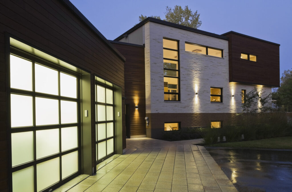 lluminated two car garage and beige stone with brown cedar wood modern cubist style residential home facade with paving stone and black asphalt driveway at dusk in summer, Quebec, Canada. This image is property released. CUPR0269