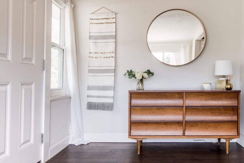 Foyer with wood console table, mirror, and wall tapestry