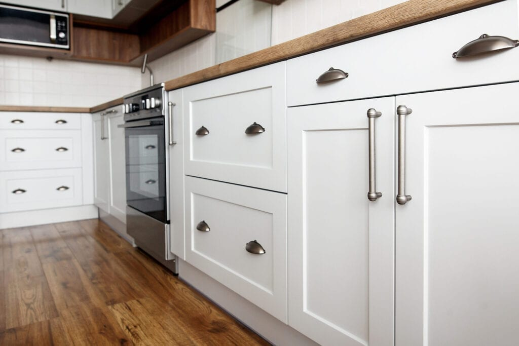 Close up of white kitchen cabinets with wood countertop and brass handles