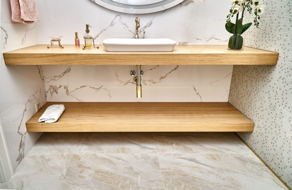 Floating wooden basin countertops with white ceramic sink and golden tap in contemporary apartment