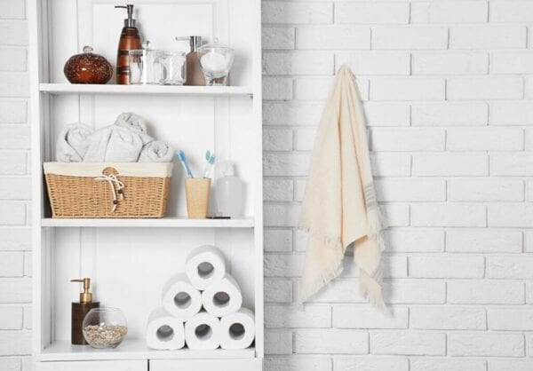 Using vertical storage space in small bathroom with tall shelves and wall hooks