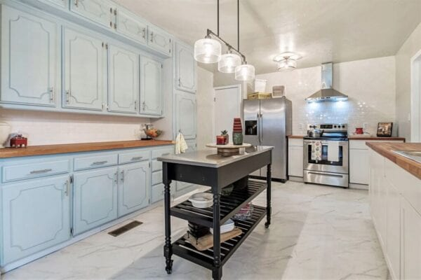 Traditional style kitchen with marble floors and rolling island