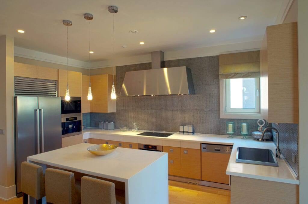new luxury kitchen in a modern home mansion. A modern kitchen with granite counters, stainless steel appliances, and a tile backsplash.