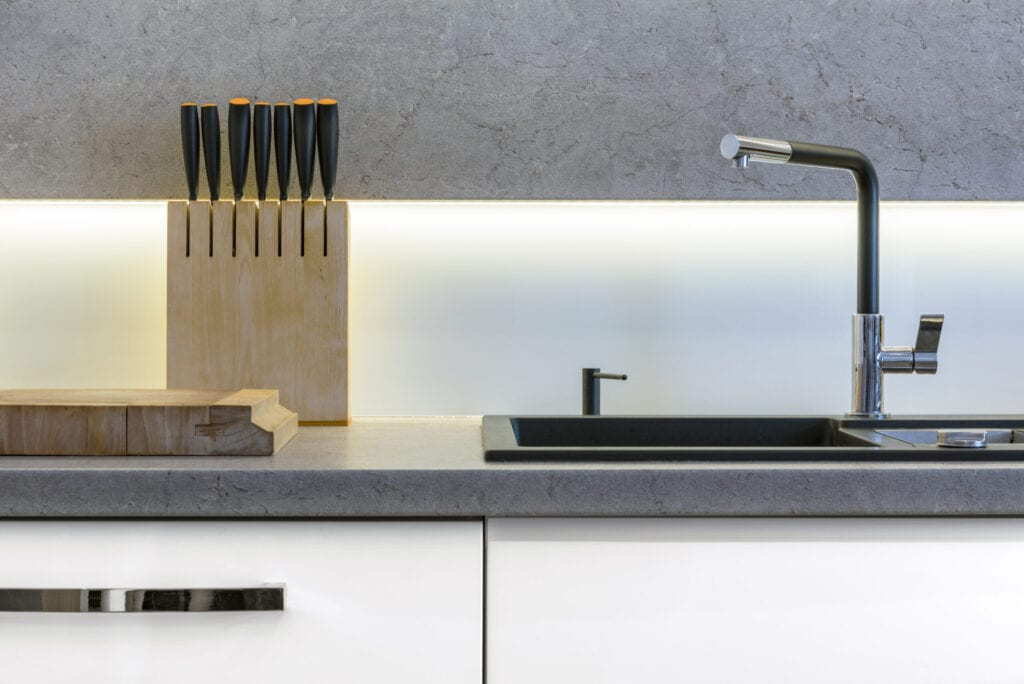 Detail of modern kitchen with knifes, sink and wooden cutting board