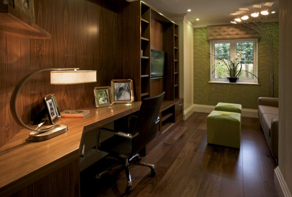 A beautiful dark-wood paneled office room in a luxury penthouse apartment. The flooring is made from solid walnut. This is a show home for a luxury development and has been furnished by an interior designer. Two green footstool cubes are illuminated by an unusual corner lamp unit. A large desk lamp illuminates the desk top. All framed images are included in my iStock portfolio.