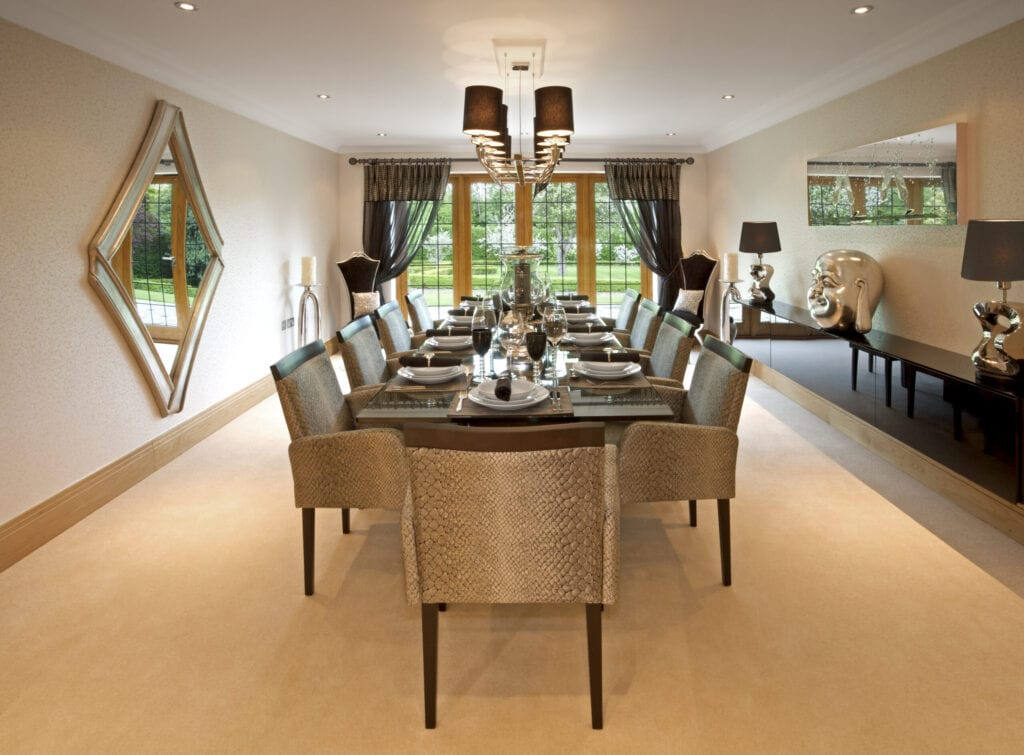 A large dining room in a luxury new home, tastefully decorated by a leading Interior Designer. A long eight-seat table has been set for lunch or dinner.