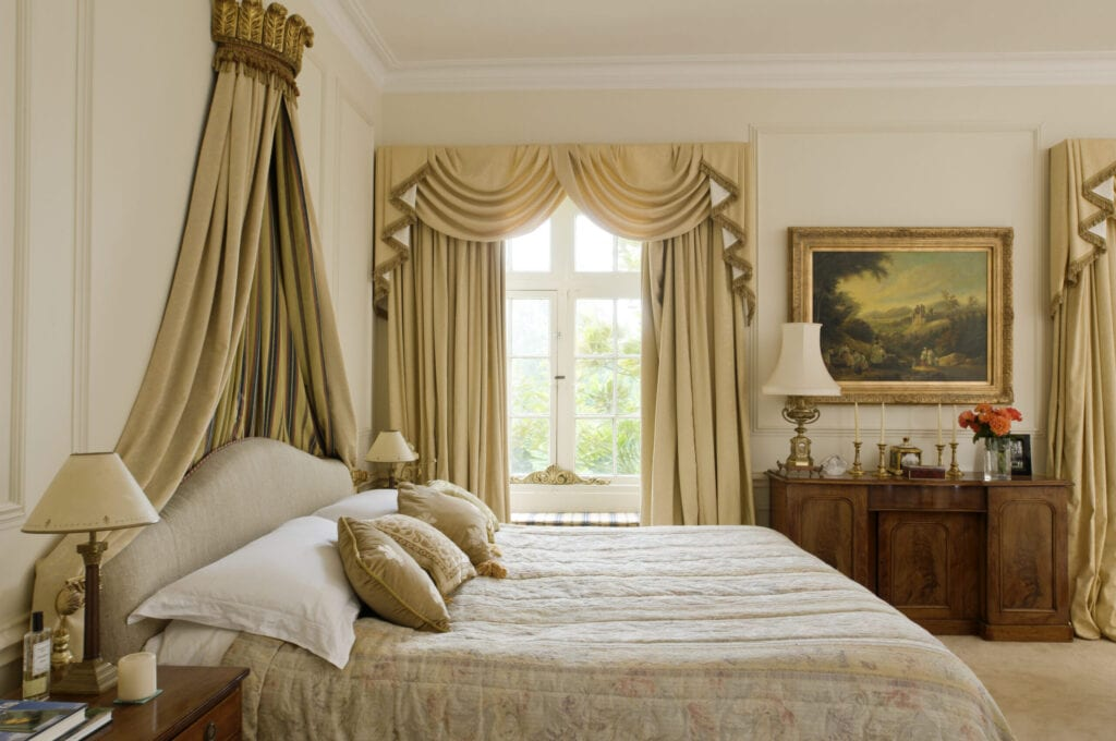 Bed with gilt coronet in bedroom with full length pale gold curtains, Ampney Park, 17th century english country house